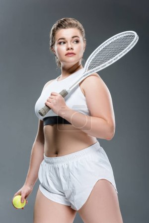 attractive overweight woman holding tennis racquet and looking away isolated on grey