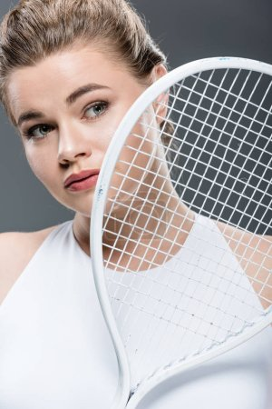 beautiful young oversize woman holding tennis racquet isolated on grey