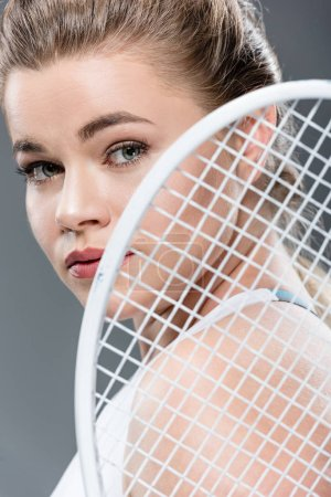 close-up view of young woman holding tennis racket and looking at camera isolated on grey