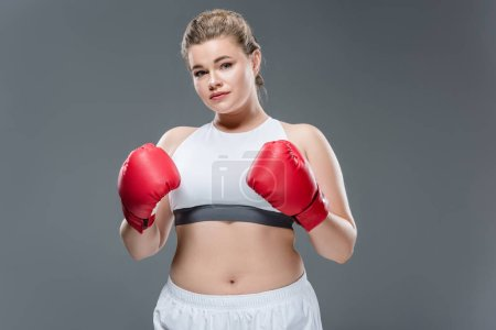 attractive size plus woman in sportswear and boxing gloves looking at camera isolated on grey