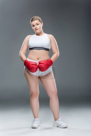 full length view of young overweight woman in sportswear and boxing gloves looking at camera on grey