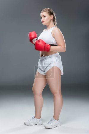 young oversize woman in sportswear training in boxing gloves on grey