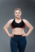 beautiful young overweight woman in sportswear standing with hands on waist and looking at camera isolated on grey