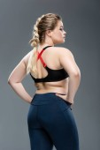 back view of young overweight woman in sportswear standing with hands on waist isolated on grey