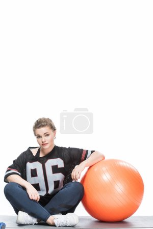 young overweight woman in sportswear leaning at fit ball and sitting on yoga mat isolated on white