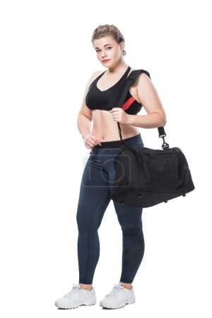 full length view of attractive young size plus woman with sports bag looking at camera isolated on white