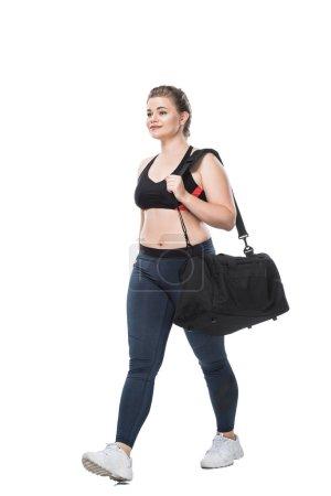 Photo pour Souriante jeune taille plus femme avec sac de sport marche et à la recherche de suite isolé sur blanc - image libre de droit