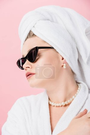 close-up view of young overweight woman in bathrobe, sunglasses and towel on head looking away isolated on pink