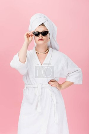 young oversize woman in bathrobe, sunglasses and towel on head standing with hand on waist isolated on pink