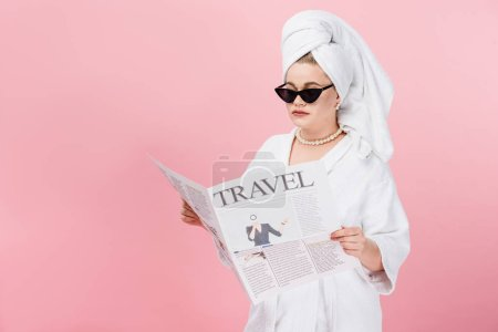 young oversize woman in bathrobe, sunglasses and towel on head reading travel newspaper isolated on pink
