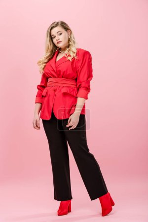 vue de la pleine longueur de belle femme oversize en élégant costume élégant regardant la caméra sur rose