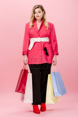 full length view of beautiful stylish young oversize woman with shopping bags looking at camera on pink