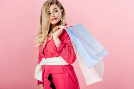 attractive stylish oversize girl holding shopping bags and looking away isolated on pink