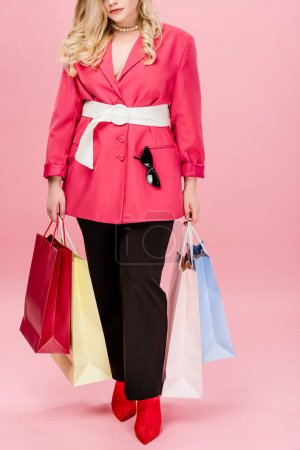 cropped shot of stylish size plus woman holding shopping bags on pink