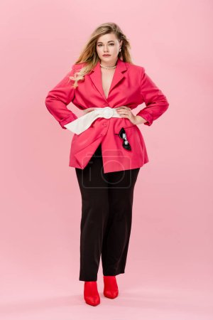 full length of beautiful fashionable plus size woman standing with hands on waist and looking at camera isolated on pink