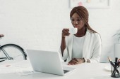 african american adult businesswoman in white suit sitting at computer desk, holding cup of coffee and working at office