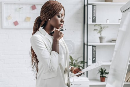 pensive african american adult businesswoman in white formal wear holding document and working on project near flip chart in office