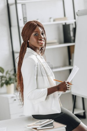 smiling african american adult businesswoman in white formal wear working on project, holding document and looking at camera in office