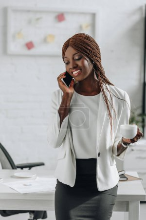 smiling african american adult businesswoman in white formal wear talking on smartphone and holding cup of coffee in office