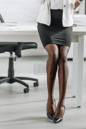 cropped view of legs of african american businesswoman in formal wear in office