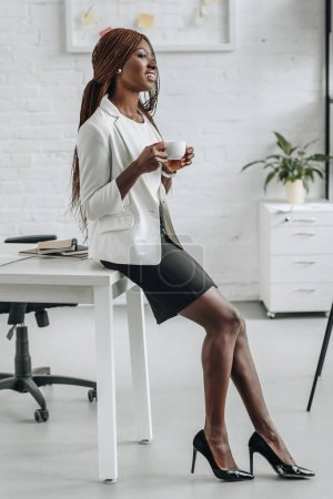 african american adult businesswoman in white formal wear leaning on office desk, smiling and holding cup of coffee
