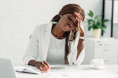 Photo for Tired african american adult businesswoman sitting at desk and working on project in office - Royalty Free Image