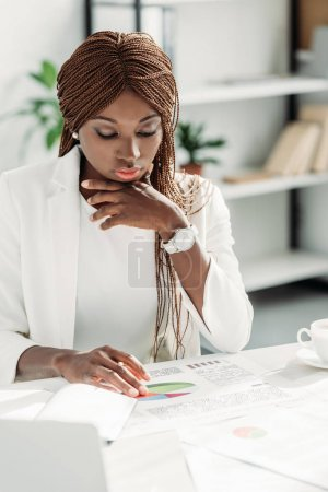 pensive african american adult businesswoman sitting at desk and working on project