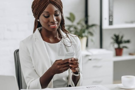Photo for Smiling african american adult businesswoman in white formal wear sitting at desk and using smartphone in office - Royalty Free Image