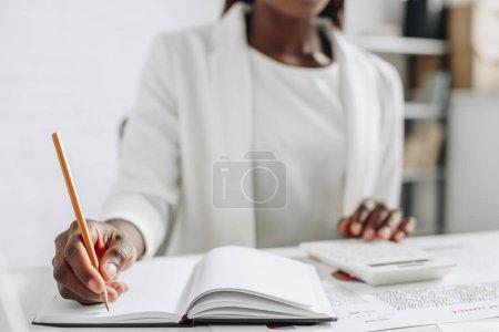 Photo pour Mise au point sélective d'une femme d'affaires adulte afro-américains en vêtements blancs écrire dans cahier et travaillant au bureau - image libre de droit