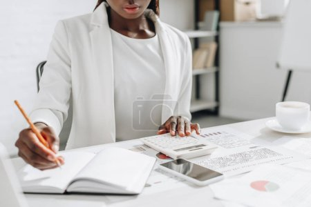 cropped view of african american adult businesswoman in white formal wear writing in notebook and working at office desk