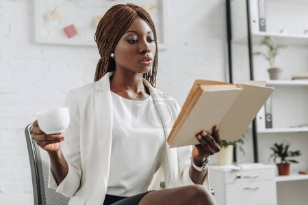 serious african american adult businesswoman in white formal wear reading book and holding cup of coffee in modern office