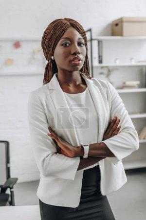 confiante femme afro-américaine en vêtements blancs avec les bras croisés debout et regarder la caméra dans le Bureau
