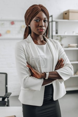 serious confident african american businesswoman in white formal wear with arms crossed standing and looking at camera in office