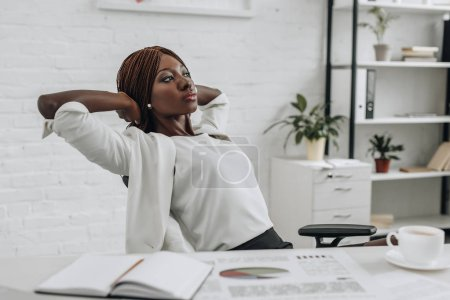 Photo pour Femme d'affaires adulte afro-américains en vêtements blancs avec les mains derrière la tête, assis au bureau et se détendre au bureau moderne - image libre de droit