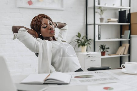 Photo for Beautiful african american adult businesswoman in white formal wear with hands behind head sitting at desk and relaxing at modern office - Royalty Free Image
