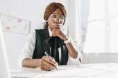 african american female adult architect in glasses using pen and working on documents in office