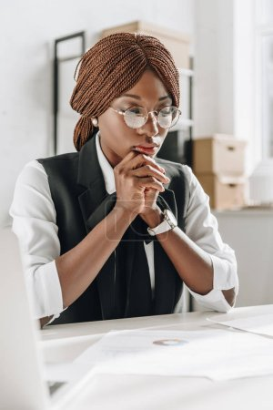 pensive african american female adult architect in glasses working on documents in office