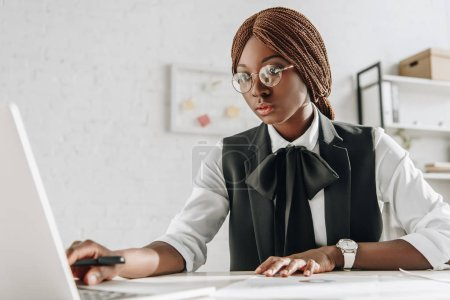 attractive focused african american adult businesswoman in glasses sitting at computer desk and working in office
