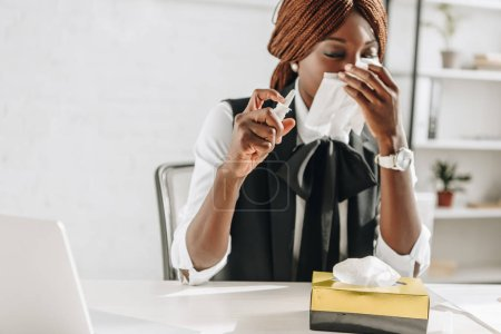 sick african american adult businesswoman suffering from cold and using tissues at desk in office