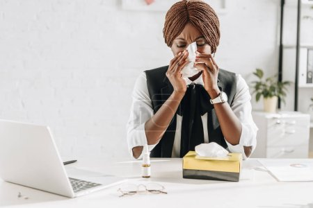 ill african american adult businesswoman suffering from cold and using tissues at desk in office