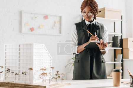 african american female adult architect in glasses writing in notebook and working on construction project in office