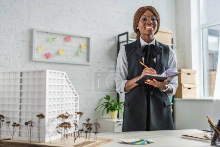 Photo pour Souriant afro-américaine architecte adulte femelle dans des verres en regardant la caméra écrire dans cahier et travaillant sur le projet de construction dans le Bureau - image libre de droit