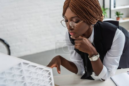 african american female adult architect in glasses and formal wear touching chin with hand and working on construction project