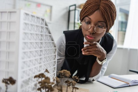 serious african american female adult architect in glasses and formal wear touching chin with hand and working on construction project