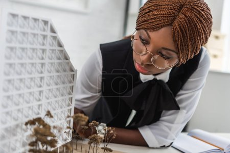 focused african american female adult architect in glasses and formal wear working on construction project
