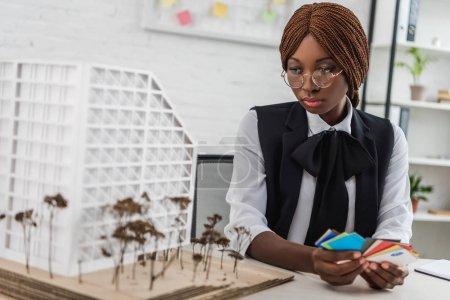 Foto de Centrado a arquitecto adulto mujer afroamericana en vasos que muestras de color y trabajando sobre proyecto de construcción en la oficina - Imagen libre de derechos