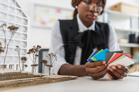 Photo for African american female adult architect in glasses holding color swatches and working on construction project in office - Royalty Free Image