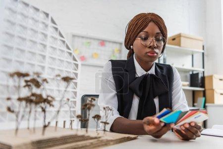 Foto de Atractivo arquitecto adulto mujer afroamericana en vasos que muestras de color y trabajando sobre proyecto de construcción en la oficina - Imagen libre de derechos
