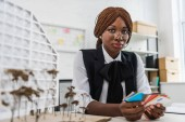 beautiful african american female adult architect in glasses holding color swatches, looking at camera and working on construction project in office