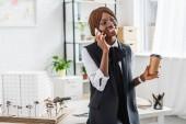 feliz adulto americano africano mujer arquitecto en gafas hablando en smartphone y celebración de café en oficina